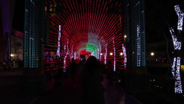 mensen lopen van de wijk rond de kerstverlichting 's nachts