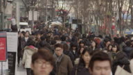 People walking down a crowded Seoul street in slow motion