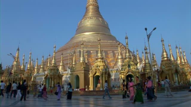 People walking in front of golden pagoda in Yangon, Myanmar