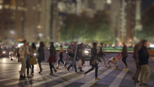 people walking in the city at night. pedestrians crossing street. commuters background