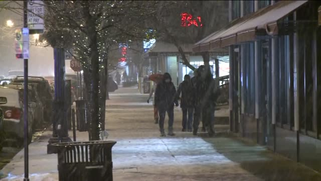 WGN People Walking In The Snow In Downtown Chicago At Night on February 08 2013 in Chicago Illinois