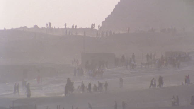 HA WS people walking near pyramid during dust storm/ Egypt