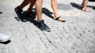 People walking on cobbled stone pavement