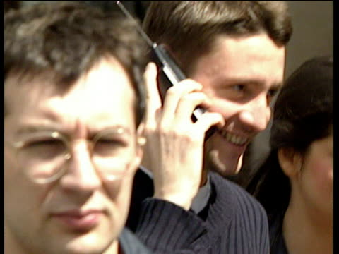 People walking on crowded streets talking on old style mobile phones