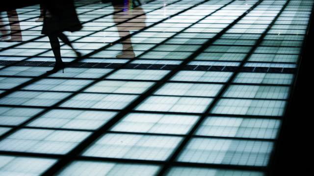 People walking on illuminated walkway in Tokyo, Japan