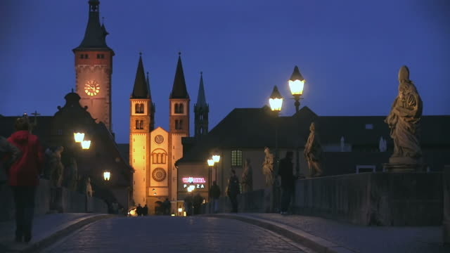 MS People walking on old main bridge infront of cathedral at night / Wurzburg, Bavaria, Germany
