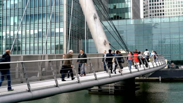 People walking on South Quay Footbridge, Canary Wharf, London UK