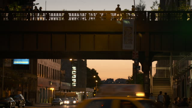 People walking on top of the Highline Park around sunset, traffic below.