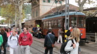 WS People walking on train platform with tram standing by at Puerto Soller near Soller / Mallorca, Balearic Islands, Spain