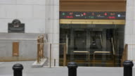 People walking pass the New York Stock Exchange stock ticker