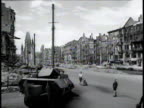 People walking past devastated buildings and burned out tank destroyer on street of postwar Berlin / Germany