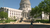 MS TU People walking past state capitol building / Madison, Wisconsin, United States