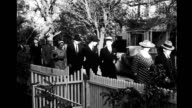 people walking past white picket fence along treelined street People walking past white picket fence on January 01 1940