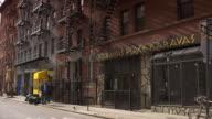 People walking the sidewalk of Cornelia Street in Greenwich Village in Manhattan
