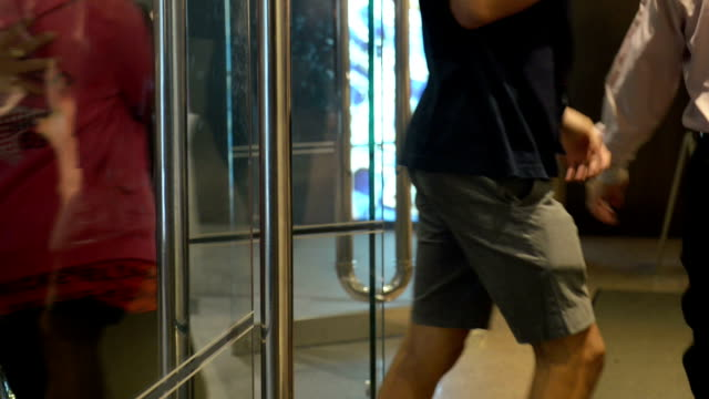 People Walking Through a Building Entrance
