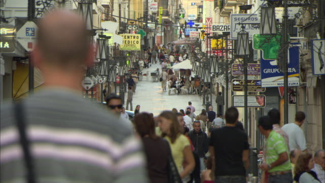 MS People walking through busy pedestrian shopping street, Ronda, Malaga Andalucia, Spain