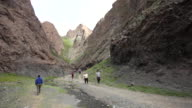 People walking through Yolyn Am, a deep and narrow gorge in the Gurvan Saikhan Mountains of southern Mongolia.