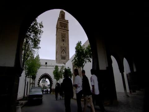 People walking under archway on street minaret in background Casablanca