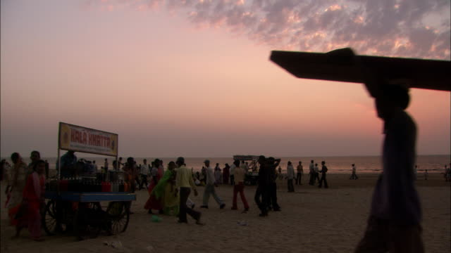 People wander about on sandy beach at sunset Available in HD.