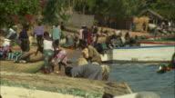 People wash clothes on the shoreline of Lake Malawi.