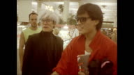 / people watch as Andy Warhol and two friends including Jock Soto walk through the B Dalton department store