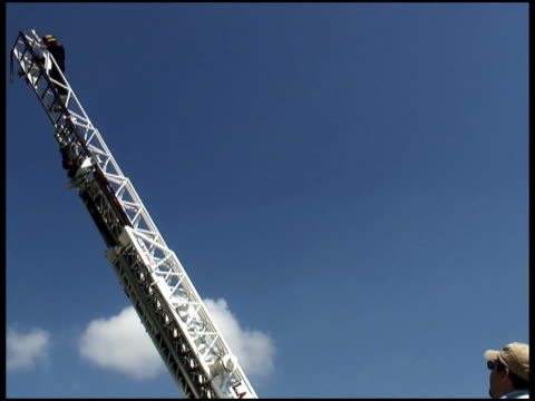 People Watch Firefighter on Rising Ladder