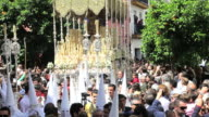 People watch the Costaleros bearing a large Trono in a procession with the hooded Nazarenos through the streets of Malaga, Andalucia, Spain, Europe