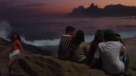 RIO DE JANEIRO-JUNE 16: People watch the ocean waves at sunset on June 16, 2013 in Rio.