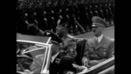 People waving Nazi flags line street Fascist dictator Benito Mussolini riding in convertible w/ Nazi Adolf Hitler Hitler Youth Jugend waving VS...