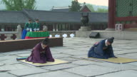MS People wearing traditional uniform bowing in revial event of joseon dynasty at gyeongbokgung royal palace AUDIO / Seoul, South Korea