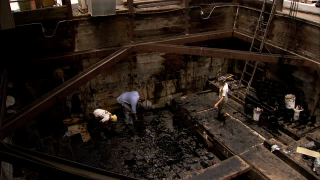 People work in the muddy basement of an empty building. Available in HD.