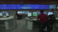 MS PAN People working at workstations, and large surveillance monitor mounted on wall in control room / Singapore City, Singapore