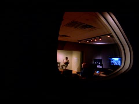 MS, PAN, People working in audio studio, view through window