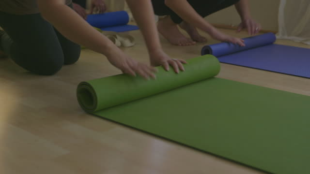 CU Peoples hands rolling mat on floor after yoga / Los Angeles, California, United States
