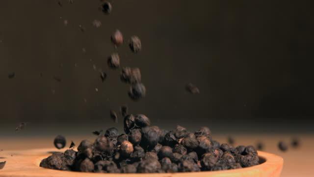Peppercorns spread in super slow motion in a wooden spoon
