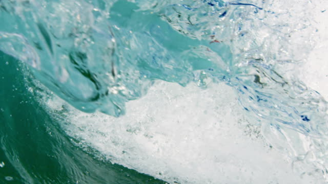 Perfect detailed beautiful wave POV as wave breaks over camera on shallow sand beach in the California summer sun. Shot in slowmo on the Red Dragon at 300FPS.
