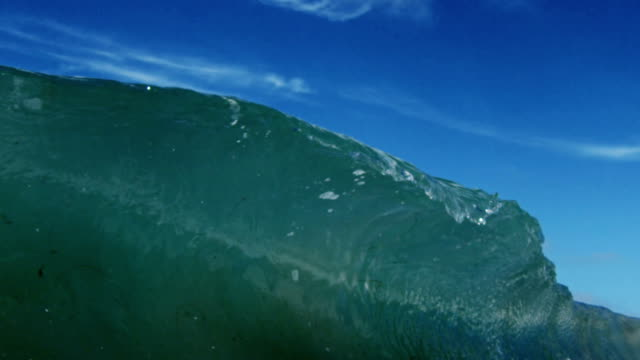 A perfect glass beautiful wave POV as wave breaks over camera on shallow sand beach in the California summer sun. Shot in slowmo on the Red Dragon at 300FPS.