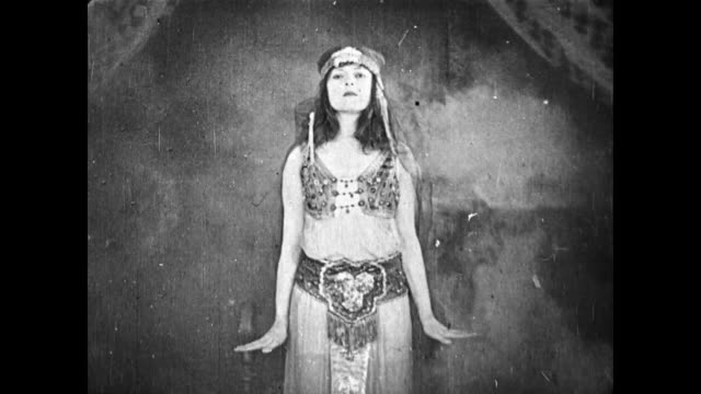 A performer (Molly Malone) dances in an Egyptian inspired scene in front of a large audience at the theater
