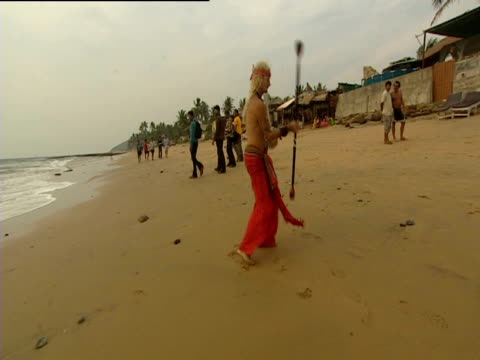 Performer in colourful costume twirling baton on the beach Goa