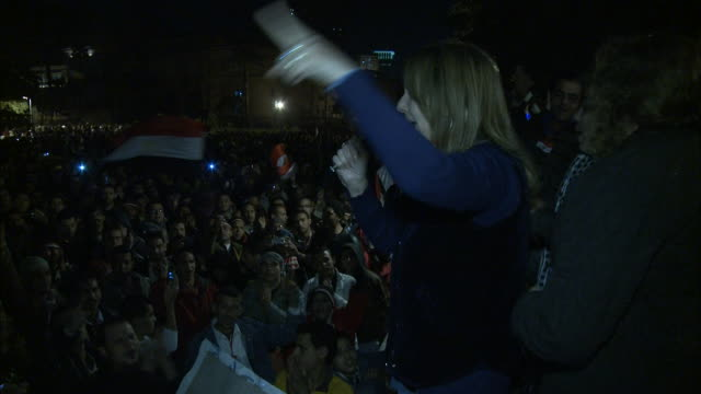 PAN Performer with microphone yelling and thrusting finger in air on stage in front of crowd in Tahrir Square during Mubarak's Speech / Cairo Egypt