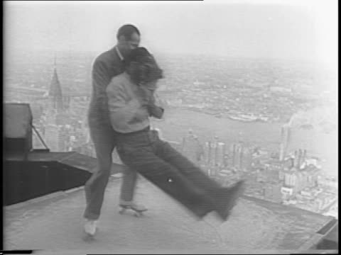 Performers roller skating on platform atop Empire State Building / stuntman Al Mingalone is spun on platform while holding camera / shot from camera...