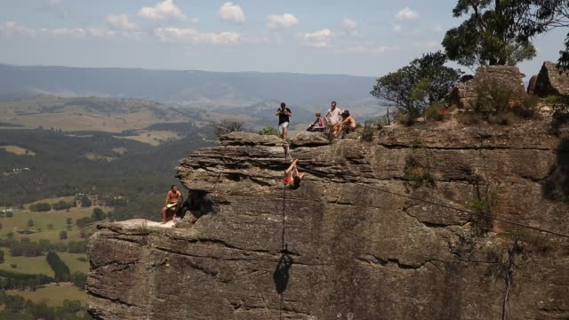 A person attempts to climb back onto a highline after falling whilst walking between cliffs at Corroboree Walls in Mount Victoria on March 8 2015 in...