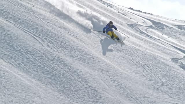 SLO MO Person backcountry skiing down sunny mountain