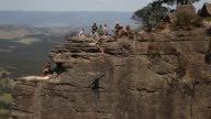 A person balances as he walks a highline rigged between cliffs at Corroboree Walls in Mount Victoria on March 8 2015 in the Blue Mountains Australia...