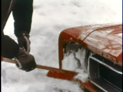 CU Person cleaning snow off headlights of red 1967 AMC Rambler Rebel / USA