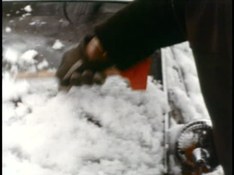 MONTAGE MS Person cleaning snow off of red 1967 AMC Rambler Rebel / USA