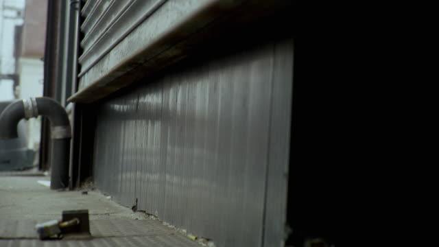 CU LA SELECTIVE FOCUS Person closing roller door of shop, Brooklyn, New York City, New York State, USA