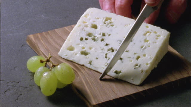 CU, Person cutting Roquefort cheese, close-up of hand