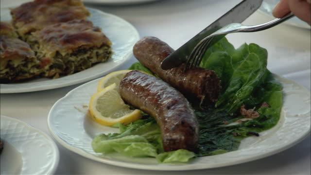 CU Person cutting sausage / Greece