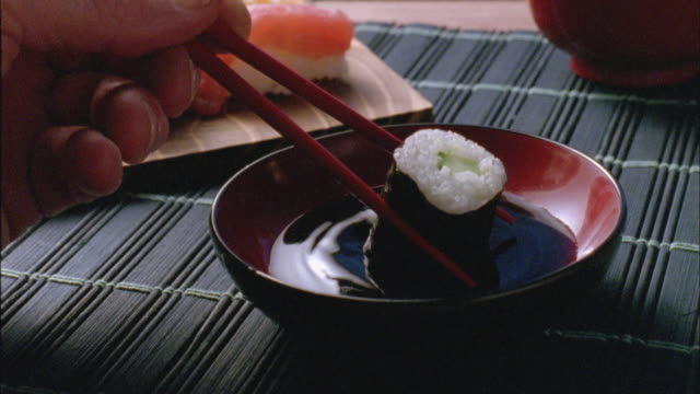 CU, Person dipping sushi roll in soy sauce, close-up of hand